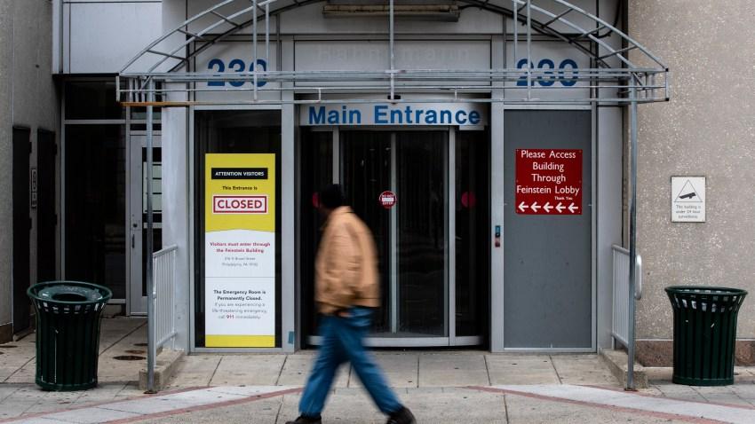 A pedestrian walks past the shuttered Hahnemann Hospital in Philadelphia, Wednesday, March 25, 2020.