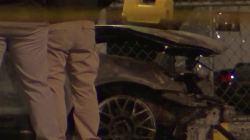Police investigate a charred car where a body was found