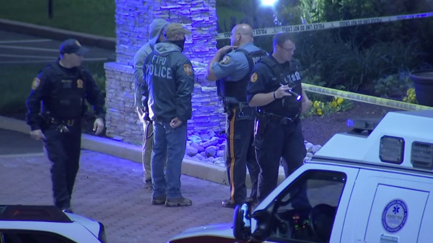 Police in Falls Township, Pennsylvania, stand outside a Holiday Inn Express hotel, where a gunman opened fire and gravely injured a man.