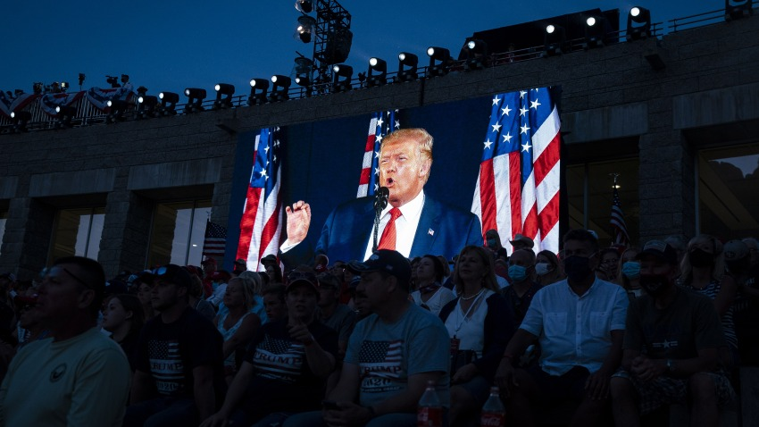 U.S. President Donald Trump is displayed on a screen as he speaks during an event at Mount Rushmore National Memorial in Keystone, South Dakota, U.S., on Friday, July 3, 2020. The early Independence Day celebration, which will feature a military flyover and the first fireworks in more than a decade, is expected to include about 7,500 ticketed guests who won't be required to wear masks or socially distance despite a spike in U.S. coronavirus cases.