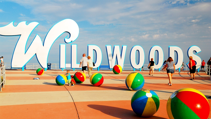 The Wildwoods sign in Wildwood, New Jersey with people walking in front of it.