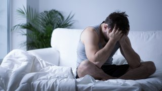 Hombre sentado en actitud de depresión o llanto
