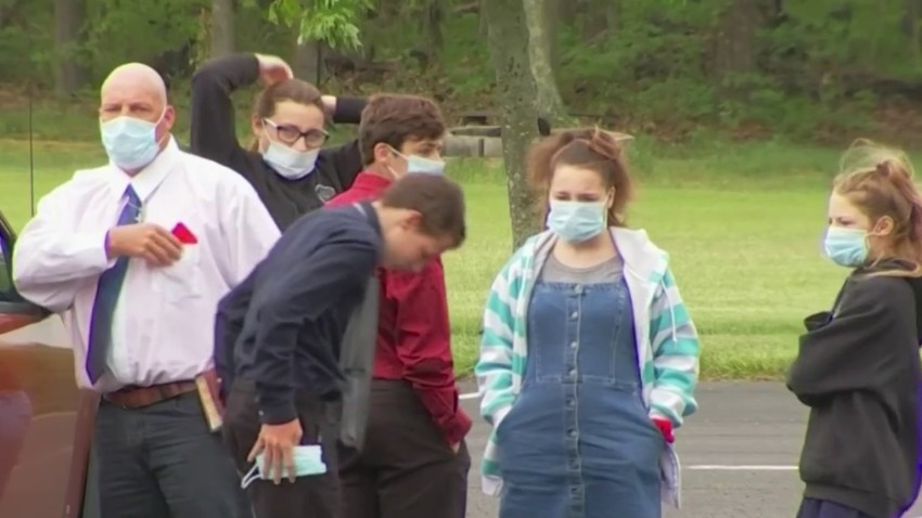 Perishioners wearing masks gather outside Solid Rock Baptists Church in Camden County, New Jersey.