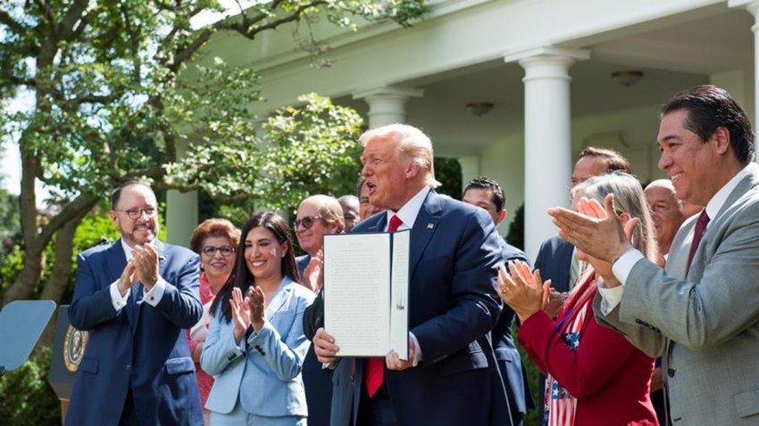 El presidente de EE.UU., Donald J. Trump (c), sostiene la orden ejecutiva con la que crea la Comisión de Asesores para la Prosperidad de los Hispanos, este 9 de julio de 2020, en la Casa Blanca, Washington.