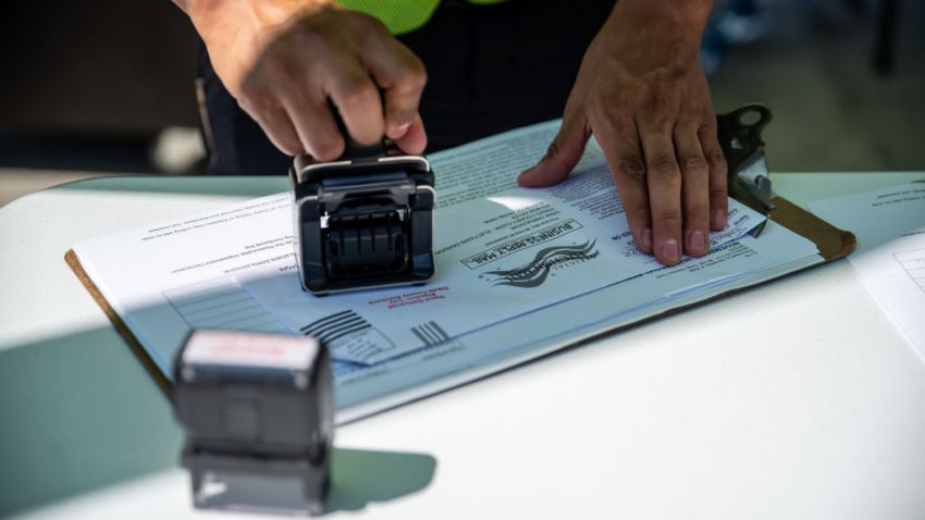 A worker stamps a ballot at a drive-thru mail ballot hand delivery center in Austin, Texas, U.S., on Friday, Oct. 2, 2020. Governor Abbott announced that every county in Texas would only be allowed one drop off box for mail in ballots, citing concerns of voter fraud.