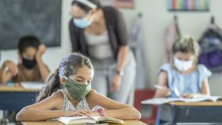 Young female student wearing a protective face mask in the classroom