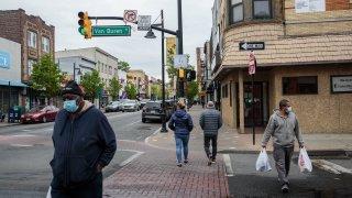 Pedestrians wearing protective masks walk through the Ironbound district of Newark, New Jersey