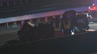 A car rests on its roof as emergency crews surround it after a crash on the New Jersey Turnpike.