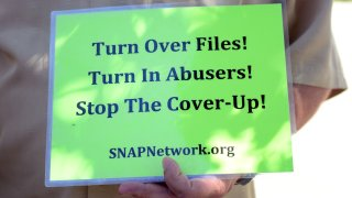 Someone holds up a sign for SNAPNetwork.org