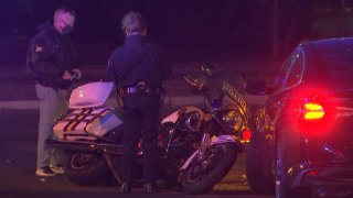 Two Philadelphia police detectives look on at a Philadelphia Highway Patrol motorcycle that rests on its side and is in front of a dark-colored sedan following a crash in which the officer on the motorcycle had to be hospitalized.