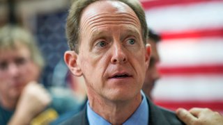 Sen. Pat Toomey, R-Pa., in front of a red white and blue background