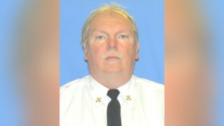 John Evans, a Philadelphia firefighter who died of COVID-19, wears a white button-up shirt and black tie as he stares ahead in a portrait photo.