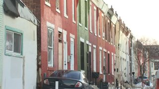 Brick row homes stand next to one another. A black sedan is parked in front of one of them.