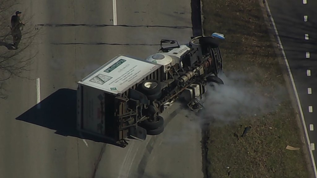 A box truck rests on its side as smoke wafts from it. The truck lays across multiple lanes of traffic.
