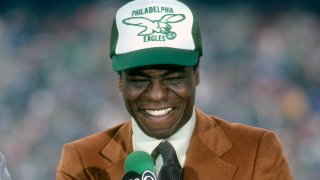 Analyst Irv Cross in an Eagles hat with a microphone