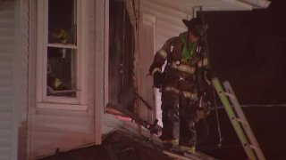 A firefighter stands on a roof, in front of a ladder, and looks down after a fire at a South Jersey home.