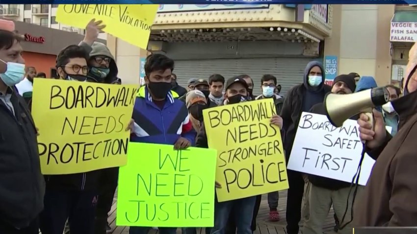 """Atlantic City business owners hold up signs reading """"We need justice"""" and similar slogans after another business owner died following a robbery by a group of kids."""