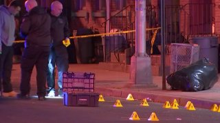 Several evidence markers are seen on the ground while investigators look on at the site of a shooting in Trenton, New Jersey.