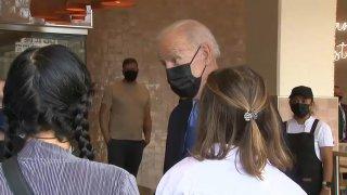 President Joe Biden speaks a woman from Philadelphia at a Washington, D.C., restaurant