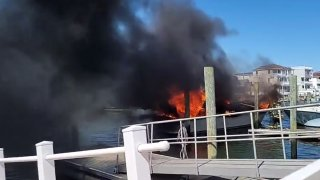 Flames and black smoke billow from a boat at a harbor in Wildwood, New Jersey.