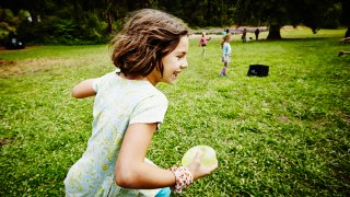 Girl runs with a water balloon on a green lawn