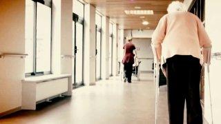 Woman using walker in nursing home hallway