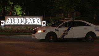 "A Philadelphia police cruiser parks in front of a sign reading ""Alden Park."""