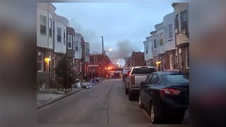 Cars are parked on a street line by row homes as a smoke and flames rise from a fire over the horizon.