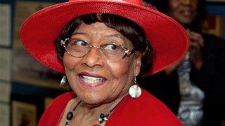 Ex-Camden Mayor Gwen Faison smiles as she wears a hat.