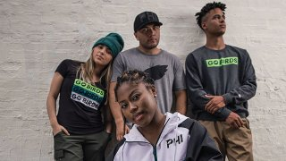 """A woman in a zip-up jacket with the letters """"PHI"""" embroidered on it crouches as another woman and two men stand behind her. The woman on the far left wears a t-shirt saying """"Go Birds,"""" as well as a beanie. The man in the center wears a gray t-shirt with a black logo of the Philadelphia Eagles. The man on the right wears a sweater with the words """"go birds"""" printed across the chest."""