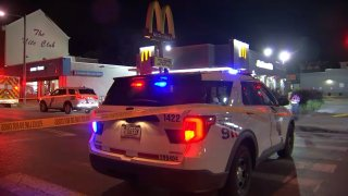 Crime scene tape runs across the back of a Philadelphia police SUV that is parked in front of a McDonald's.