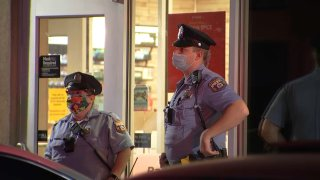 Two Philadelphia police officers in uniform wear face masks as they stand outside a Wawa store following a deadly shooting.